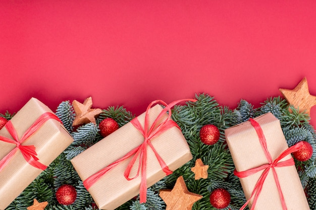Рождественская композиция. рождественские красные украшения, еловые ветки с игрушками подарочные коробки на красном фоне. плоская планировка, вид сверху, копия пространства