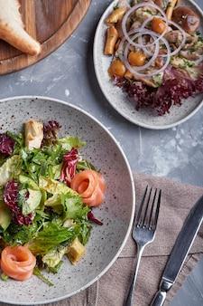 ほうれん草、コーンサラダ、ほうれん草、フレッシュミント、バジルのサーモンサラダ。手作りの料理。美味しくて健康的な食事のコンセプト。暗い石の表面。上面図。閉じる。