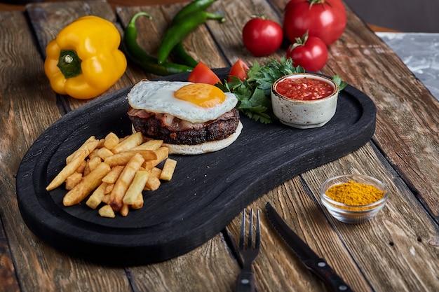 Стейк из говядины с яйцом и салатом из зелени и овощей. деревянная поверхность, сервировка стола, изысканные блюда