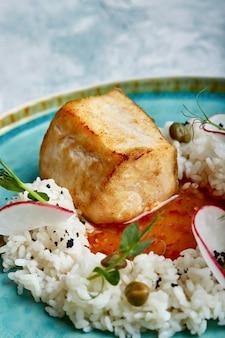 Стейк из трески с рисом и соусом на синюю тарелку на поверхности бетона.