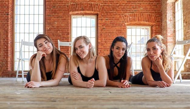 Красивые девушки лежат на полу. концепция женской дружбы, красоты и успеха. женские компаньоны в спортзале отдыхая после фитнеса, крытого во всю длину.