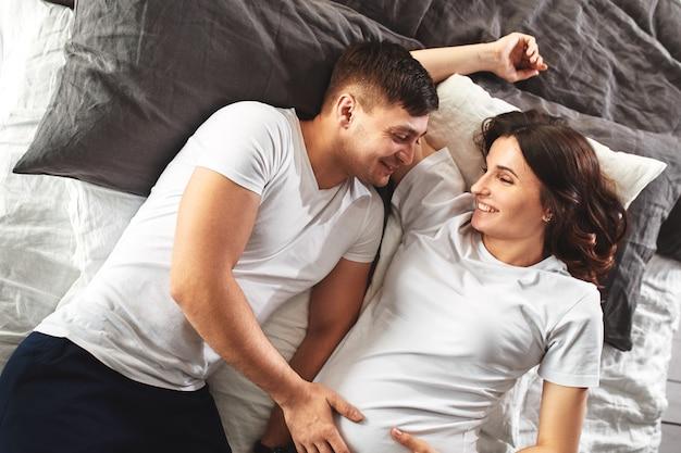 赤ん坊を待っている若い夫婦。寝室に横たわっている美しいカップルは、赤ちゃんの誕生の計画を立てます。最初の子供、産後、若い家族。