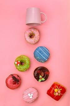パステルカラーのバラの表面にアイシングとコーヒーカップとカラフルなドーナツ。甘いドーナツ。