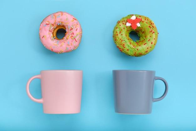 パステルブルーの表面にアイシングとコーヒーカップとカラフルなドーナツ。甘いドーナツ。