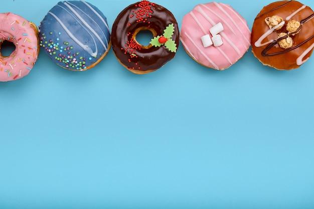 コピースペースと青色の背景に各種ドーナツの平面図です。カラフルなドーナツの背景。振りかけるとさまざまな艶をかけられたドーナツ。