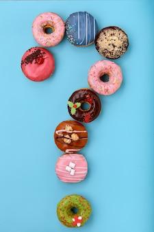 Вопросительный знак из глазированных красочных пончиков на синей поверхности