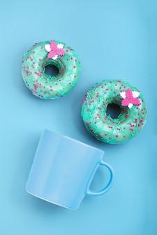 パステルブルーの表面にアイシングとコーヒーカップと青いドーナツ。甘いドーナツ。