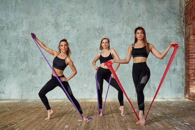 Три улыбающиеся красивые, фитнес девушки позируют в тренажерном зале. концепция спорта, работа в команде.