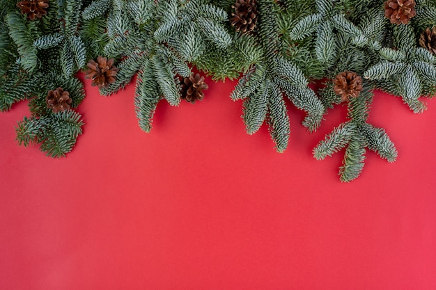 Рождественская композиция. рождественские красные украшения, еловые ветки с шишками на красном фоне. плоская планировка, вид сверху, копия пространства