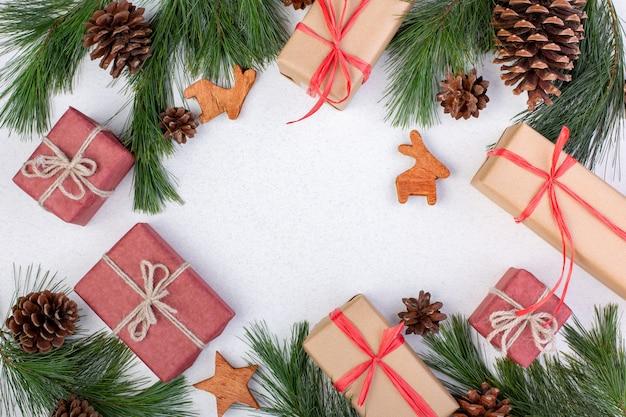 Рождественская композиция. украшения рождества белые, ветви ели с подарочными коробками игрушек на белой предпосылке. плоская планировка, вид сверху, копия пространства, открытка