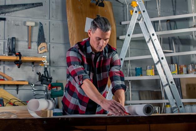 Плотник работает. карпентер изучает чертежный проект. на фоне мастерской