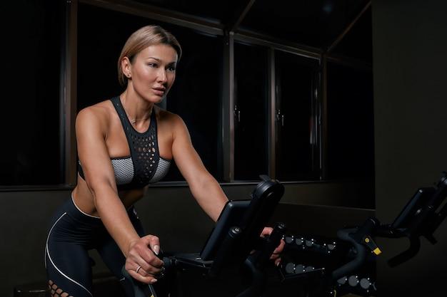 屋内で自転車で運動する若い自信を持って女性アスリート。暗いジムでサイクリングの練習をしている魅力的な決定されたフィットネス女の子。スポーツ少女の機能トレーニングトレーニング。カーディオトレーニング