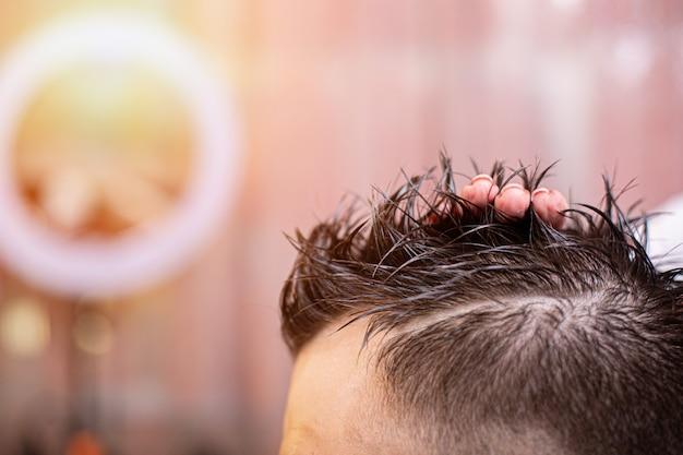 Мастер укладывает волосы мужчине в парикмахерскую, парикмахер делает прическу для молодого человека с помощью геля и лака.
