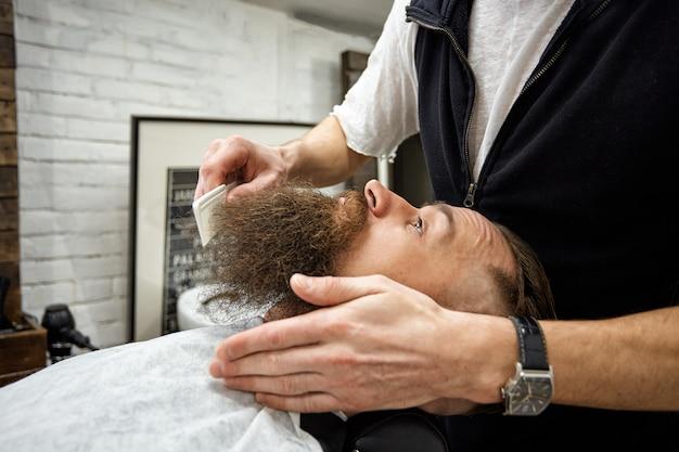 マスターバーバーはヘアスタイルとスタイリングを行います。コンセプト理髪店。ひげのスタイリングとカット。黒ひげのスタイリング。とてもおしゃれでスタイリッシュ。広告と理髪店のコンセプト
