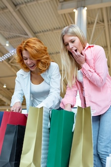 バッグをチェックショッピングセンターの美しい若い女性