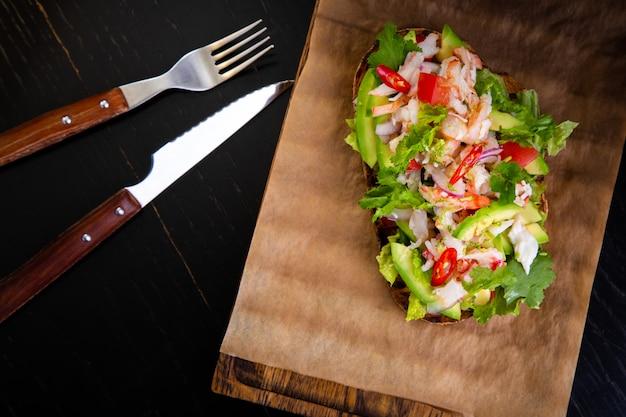 レストランのバックグラウンドでカニ肉とおいしいブルスケッタ。木の板とクラフトペーパーで提供される健康的な高級料理