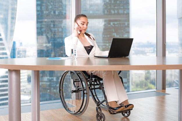無効または無効になっている若いビジネス女性人の車椅子に座ってラップトップでオフィスで働く