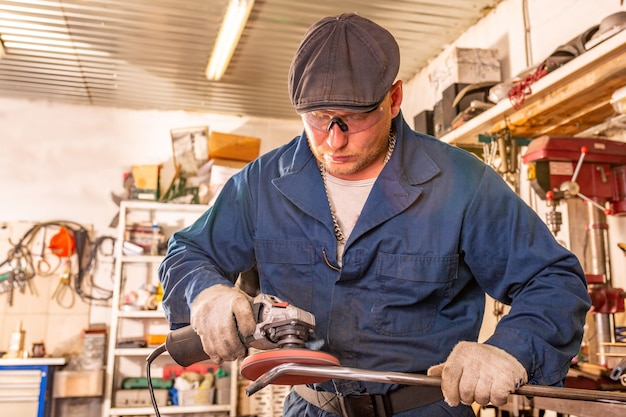Молодой человек-сварщик в синей футболке, защитных очках и перчатках обрабатывает металлическую угловую шлифовальную машину в гараже