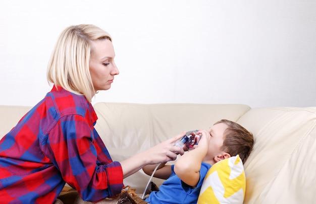 ネブライザーを介して呼吸する少年吸入中、母親は男の子の顔にネブライザーマスクを保持します。小児ネブライザーで病気の子供。