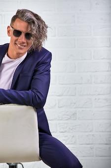 白の椅子に座ってサングラスで長い巻き毛を持つスタイリッシュなビジネスマン