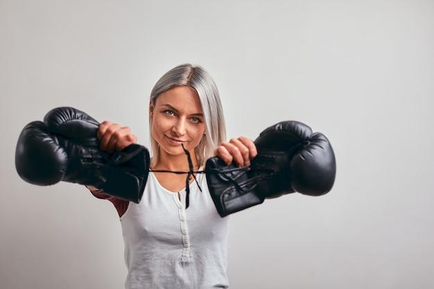Молодой красивый боксер женщины представляя с черными перчатками бокса в ее руках на сером цвете