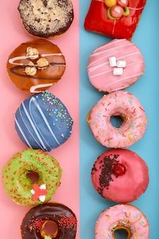青とピンクの背景に甘いドーナツ。各種ドーナツ、ボーダーカラーブルーピンクの背景。