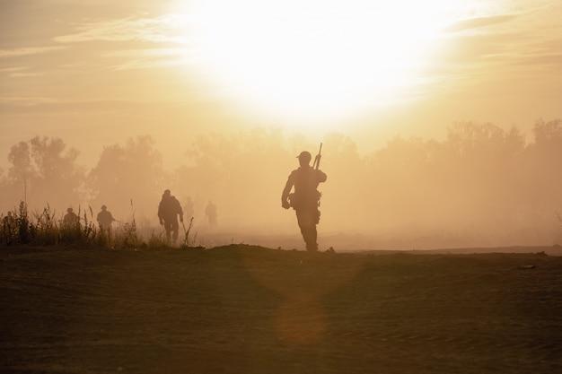 Силуэт действия солдат ходьбе держать оружие