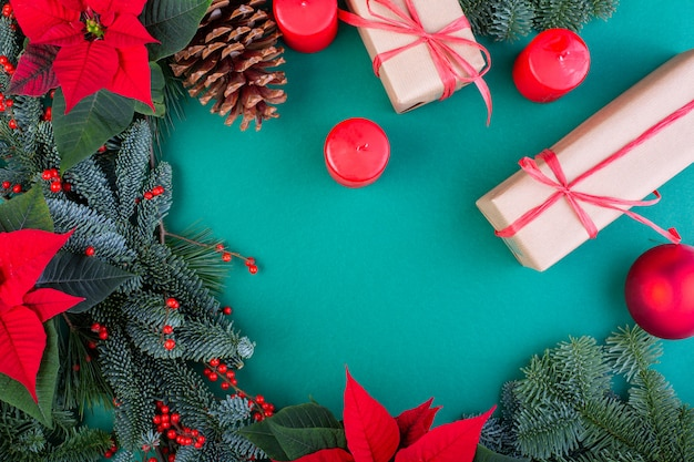 Рождественская композиция. украшения рождества зеленые, ветви ели с подарочными коробками игрушек на зеленой предпосылке.