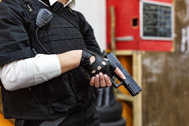 Женская рука холдинг пистолет, крупным планом. стиль боевиков