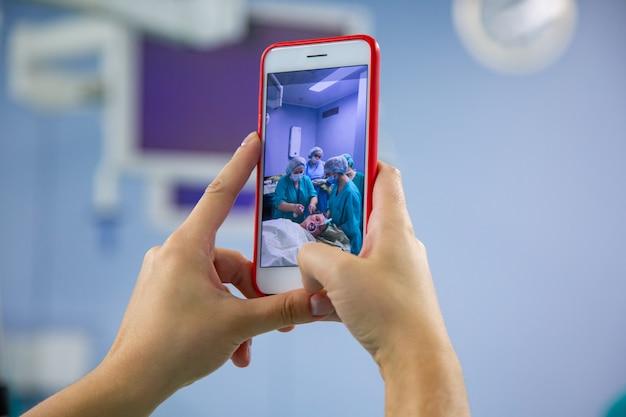 手術室からスマートフォンでのアシスタント撮影。現代の手術室で外科手術を行う医療チーム