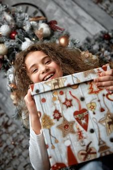 面白い笑顔のうれしそうな子供の女の子が彼の手にクリスマスプレゼントを保持しています。