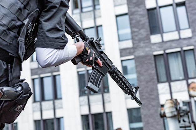銃を持っている女性の手のクローズアップ。戦争アクション映画スタイル