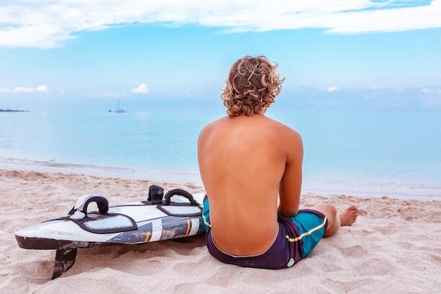 Красивый человек сидит на пляже с белой пустой доской для серфинга ждать волну для серфинга пятно на море берег океана