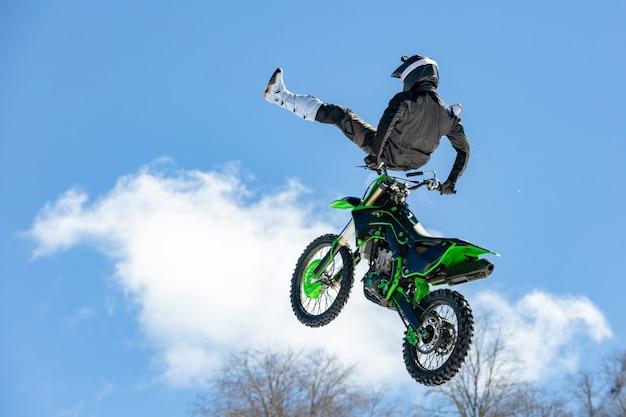 飛行中のオートバイのレーサーがジャンプし、雪山を背景に踏み台に飛び立つ