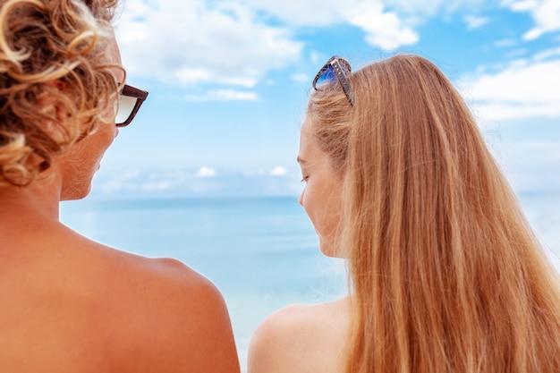 Задний портрет взгляда молодой пары в влюбленности наслаждаясь временем быть совместно на песчаном пляже.
