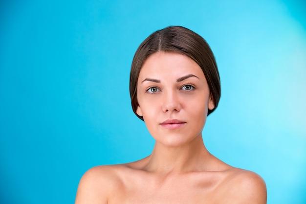 美しい女性の顔。青色の背景に笑みを浮かべてブルネットの若い女性の美しさの肖像画。パーフェクトフレッシュスキン。若さと肌ケアのコンセプトです。