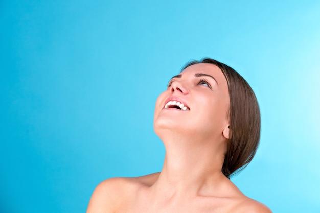 笑って、青い背景に分離されたカメラを見て完璧な肌を持つ若い魅力的な半分裸の女性の美しさの肖像画。若さと肌ケアのコンセプトです。