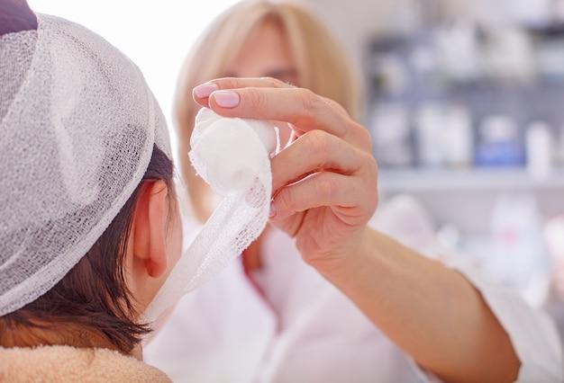 医者はクリニックで頭の患者に包帯を作ります