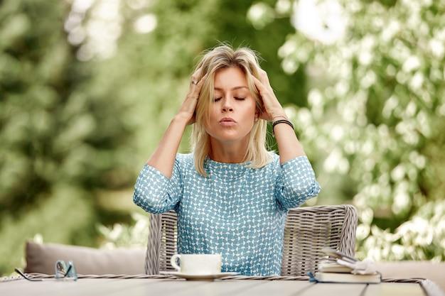 ビジネスの女性は、サマーテラスのテーブルでコーヒーを飲みながら緊張に座っています。スペース、緑のスペースをコピーします。