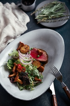 野菜と牛肉のタリアータ。クローズアップ、低いキー、灰色のスペース。