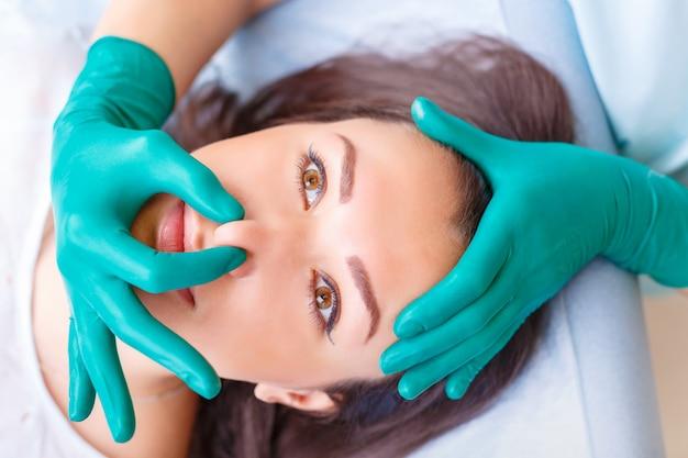 プラストの前にクリニックの女性クライアントを調べる美容整形外科医
