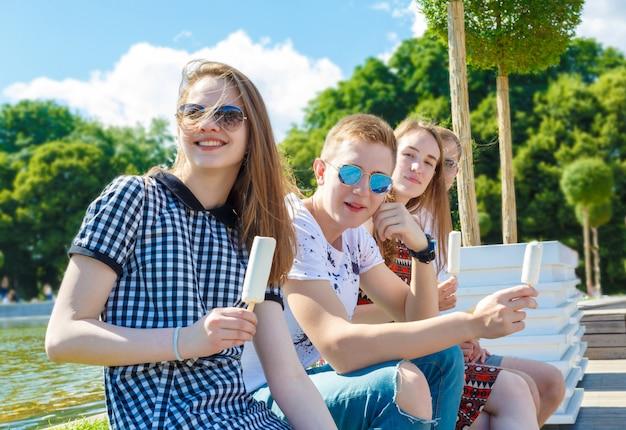 Группа улыбающихся друзей с мороженым на открытом воздухе