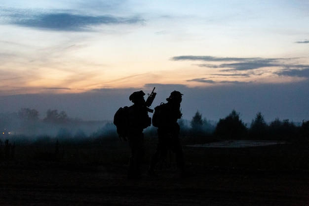 Силуэт действия солдат ходьба держать оружие фон дым и закат и баланс белого корабля эффект темного стиля арт