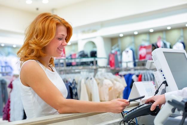 Женский клиент оплачивая с умным телефоном в магазине