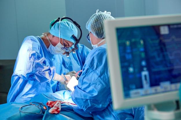 外科医の背景のぼかしチームと患者の心拍数を示す緊急治療室を運営する病院の手術の心電図