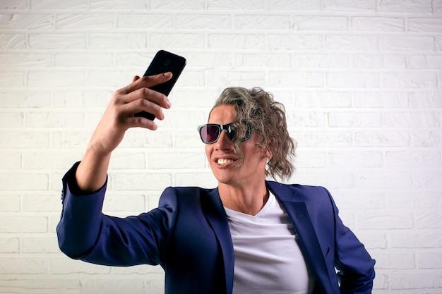 Менеджер или бизнесмен со стильными вьющимися волосами в белой футболке на белом фоне делают селфи на мобильном телефоне
