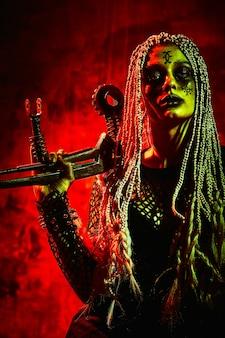 赤い背景の上でポーズのハロウィーンの衣装の女性モデル。服を着たゴージャスな女の子が死者の日を祝います。ハロウィーンのコンセプト、魔女の衣装、明るい色、スチームパンク。