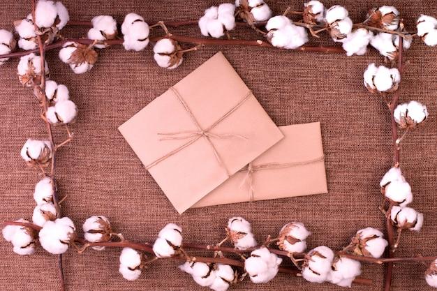 粗い茶色の黄麻布の上にふわふわの乾燥綿ボールとギフトボックスが付いている花。