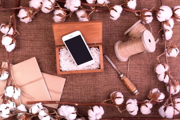 粗い茶色の黄麻布の上にふわふわの乾燥綿ボールギフトボックス、白いスマートフォンとジュートロープハンクと花します。