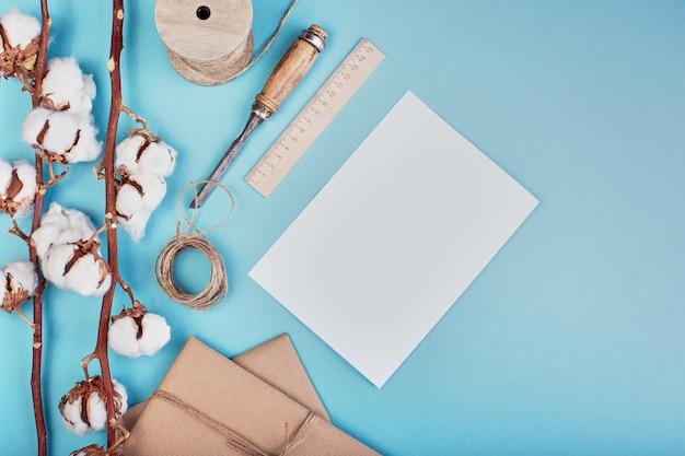 Женский светло-голубой фон с ветвью цветка хлопка. хлопок, подарочные коробки, моток джутовой веревки и чистый лист бумаги. плоская планировка, копирование пространства.